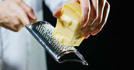 Slow motion of A cook grater Parmesan cheese, typical Italian cheese, on the plate just freshly brewed. Concept: Italian cuisine, cheese, restaurant and food.