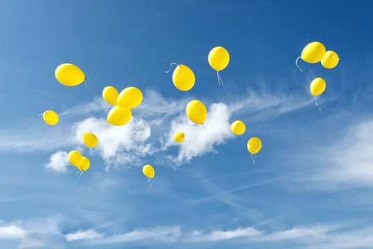 Celebration traditions. Yellow balloons in blue sky.