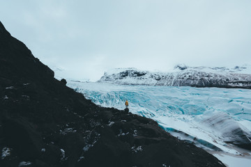 Person in yellow jacket standing in front of a glacier