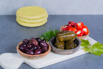 Mediterranean appetizer antipasti tapas bowls with green and calamata olives, feta cheese, stuffed pepper with garlic pita bread, herbs on white marble plank