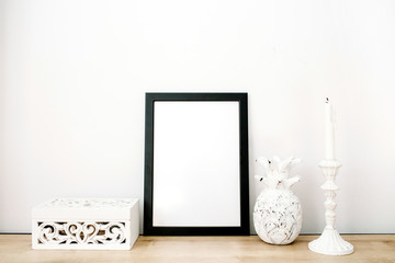 Front view blank mock up of photo frame with pineapple and trendy stuff at white background. Minimalistic decorated home office concept.