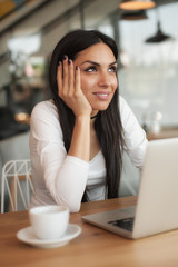 Woman in love drinks coffee and chat on laptop computer