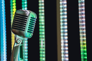 Retro style microphone on stage in the spotlight performance of the musical group. Microphone for rock music. Microphone in blue light og stage. Music is in the air. Color background.