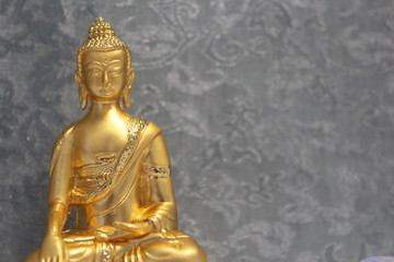 Gold Buddha Statue With a Blue Background
