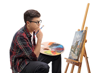 Pensive teenage painter looking at a painting