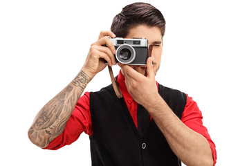 Tattooed man with a retro camera