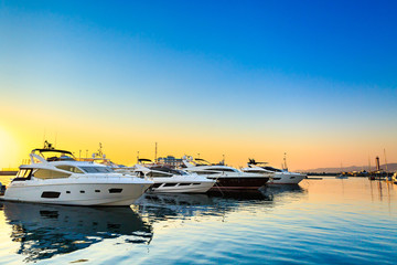 Luxury yachts docked in sea port at sunset. Marine parking of modern motor boats and blue water. Tranquility, relaxation and fashionable vacation.