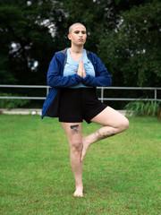 Mulher de cabeça raspada fazendo ioga