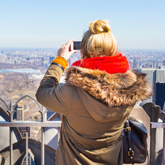 Female tourist taking a photo of New York City panorama with her smart phone from observation deck.