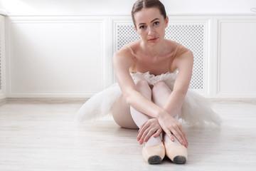 Graceful Ballerina sit on floor, ballet background