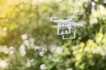 White drone quad copter with high resolution digital camera flying in the blue sky ,soft focus