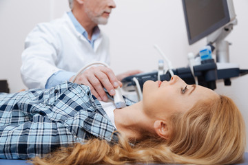 Optimistic woman getting thyroid ultrasound examination in the clinic