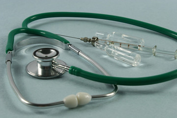 Stethoscope and syringe on blue background.