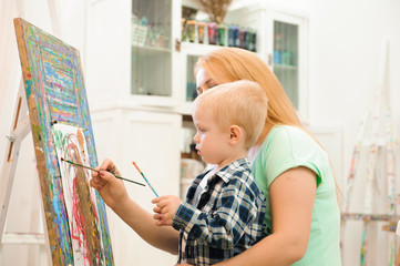 Mother and child draw a picture paints, art lesson