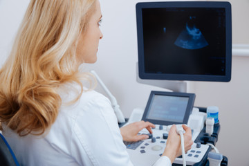Charming mature sonographer working in the clinic