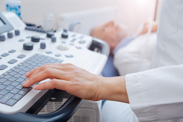 Skillful doctor using professional ultrasound equipment in the clinic