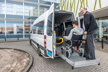 Driver Assisting Passenger In Wheelchair To Board Taxi