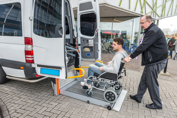 Taxi Driver Assisting Man On Wheelchair To Board Van