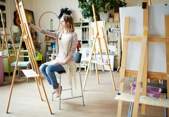 Serious girl sitting in front of easel and drawing