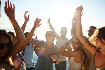 Ecstatic buddies dancing with raised hands at beach party