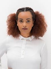 Mulher negra de cabelo crespo séria