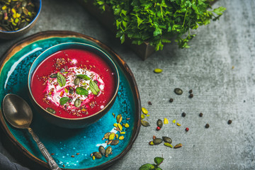Spring detox beetroot soup with mint, chia, flax and pumpkin seeds on bright blue ceramic plate over grey concrete background, copy space. Dieting, clean eating, weight loss, vegetarian food concept