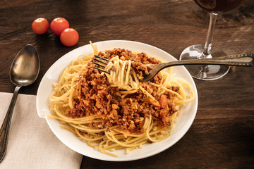 Fork over plate of pasta with meat and tomato sauce