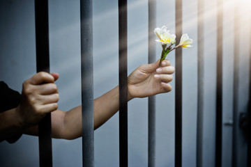 woman prisoner in prison with white flowers