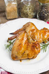 Baked chicken wings in pan on wooden table.