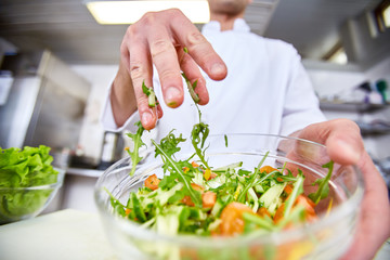 Professional chef mixing salad ingredients in bowl