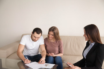 Couple meeting with female bank worker or real estate agent, signing loan agreement, mortgage contract, buying flat and getting keys of apartment, property investment, great purchase for young family