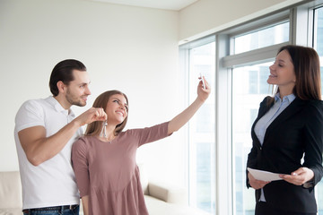 Smiling owners of new apartment making selfie on smartphone, holding keys to own home, buying house flat. Young happy couple taking photo after deal with property, standing next to real estate agent