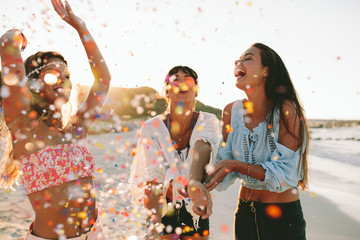 Happy young female friends enjoying party on the beach