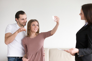 Happy apartment owners making selfie on mobile phone, showing keys to own flat, standing next to real estate agent. Young couple decided to take self-portrait photo after closing real estate deal