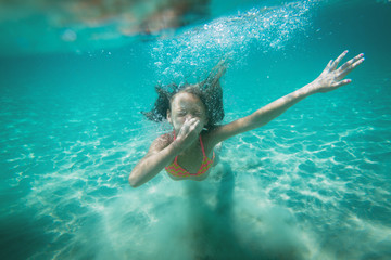 Beautiful little girl diving underwater in the sea. She is holding her nose with hand and holding breat.