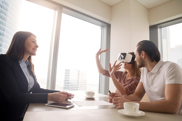Young woman wearing virtual reality glasses or goggles, couple using head-mounted display for real estate tours, excited by participation effect, virtually discover new flat, buy and sell homes in VR