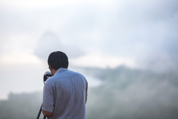 man looking photo in viewfinder of camera after taking photo of landscape