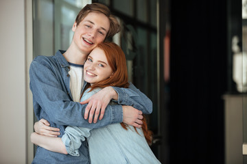 Young man and woman looking camera while hugging