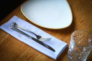 Fork and knife on a table, near a plate