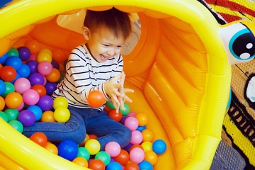 Boy playing with colored balls in the bouncy house at the Playground in the room