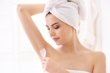 Young woman removing armpit hair with wax on blurred background
