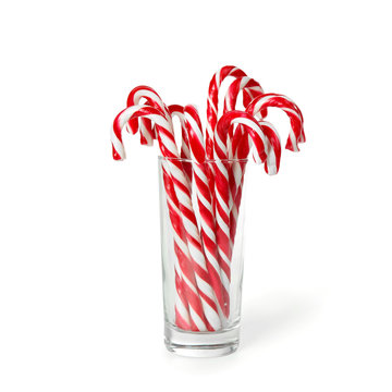 Christmas candy canes in glass on white background
