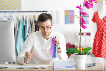 Young male fashion designer working in office