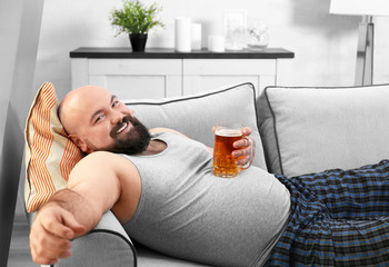 Man holding glass of beer on his big belly at home