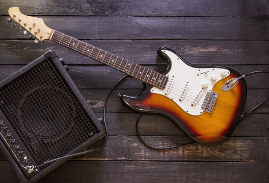 Electric guitar and amplifier connected by cable on wooden background