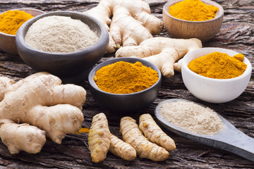 Powder and ginger root and turmeric on wood