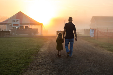 Father walking with daughter on rural road