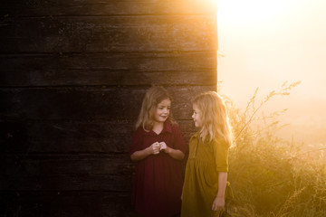 Two girls standing by barn in sunlight