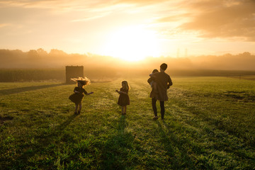Mother and daughters playing in field during sunset
