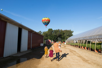 Family walking on path with hot air balloon in sky